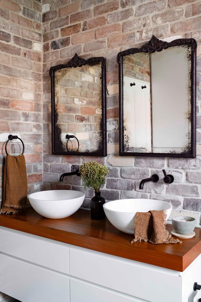 A feature wall of brick-look tiles by Steel Backed Brick Company lends another rustic note in the bathroom, completed by aged mirrors Mei had custom framed.