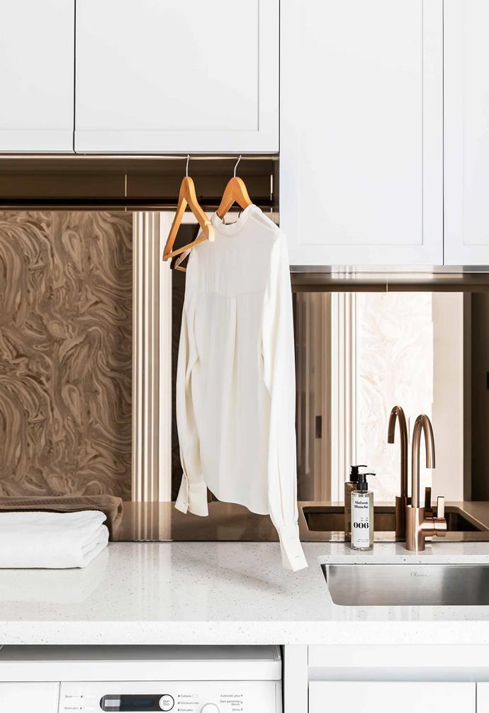 """**Laundry** The splashback is a bronze mirror that reflects the wallpaper on the opposite wall, creating a glamorous 3D effect. The brushed rose-gold tap is from [Brodware](https://brodware.com/