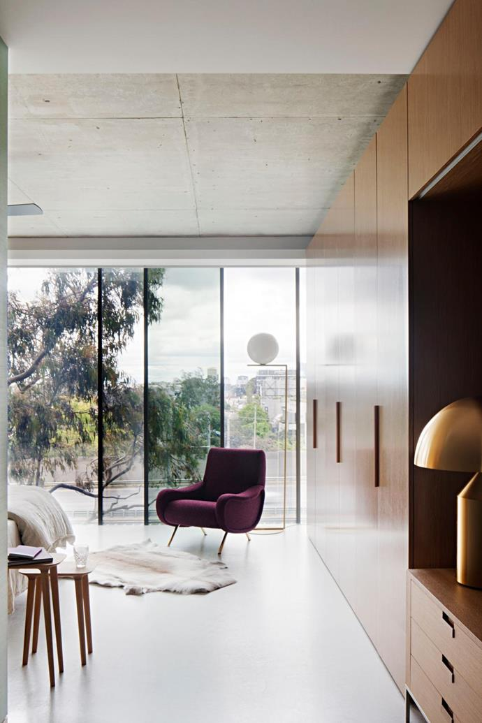 The view overlooking a park and tram tracks from the master bedroom is quintessentially urban. Cassina '720 Lady Armchair' by Marco Zanuso from Cult. 'Captain Flint' floor lamp by Michael Anastassiades from Euroluce. 'Atollo' table lamp from Euroluce. 'Bon' side tables from Apato.