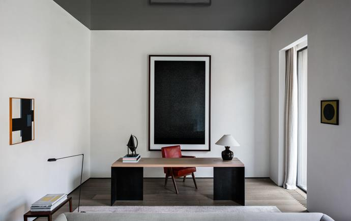 Custom-made desk in steel and brushed oak by Nicolas Schuybroek. Mid-century Pierre Jeanneret 'Senate' chair from the Chandigarh High Court, India, and a vintage Danish desk lamp. Smaller artworks by Guy Vandenbranden. Lumina Italia 'Daphine Terra' lamp accompanying the painting to the left. Behind the desk is an artwork by Tom Fecht.