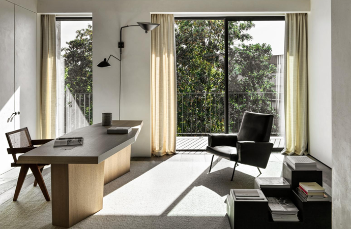 With large glass windows opening out onto lush greenery, the office space's focal point is a custom Nicolas Schuybroek solid-oak desk, accompanied by a Joseph-André Motte 'Easy' armchair. The office is further accented by Mario Bellini for B&B Italia 'Book Blocks' and a vintage Serge Mouille two-arm wall light.