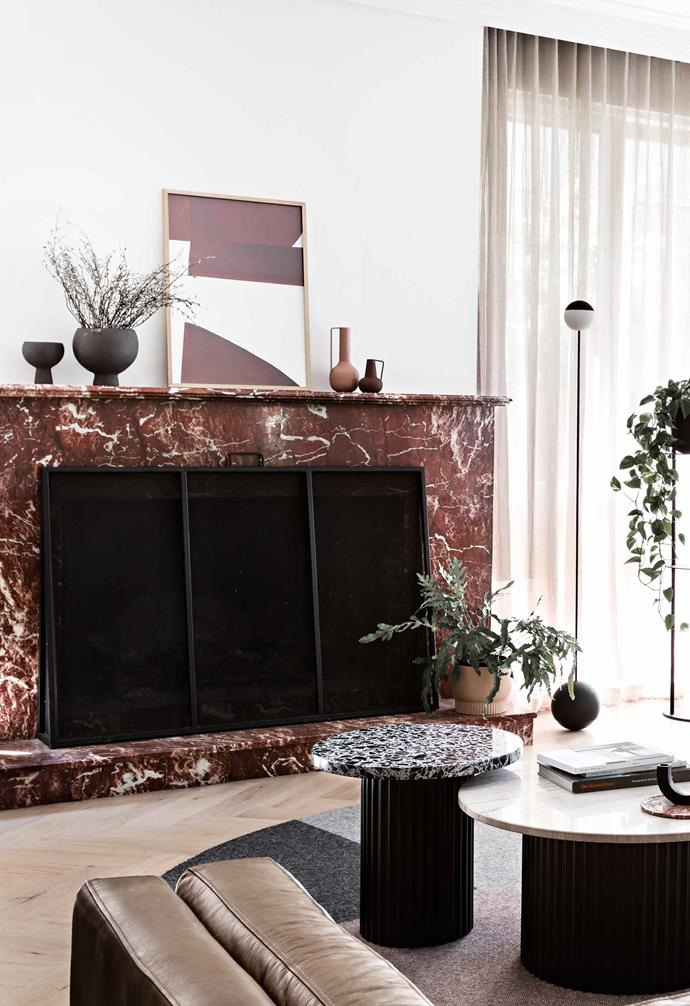 """**Living** The starting point for the renovation was the beautiful marble fireplace, which was slightly out of place in the Tudor-style home. Architect Alexandra Ansari used it as her design cue for the home's glamorous look and colour scheme. Framed Atelier CPH print and Sway floor lamp, [Designstuff](http://www.designstuff.com.au/