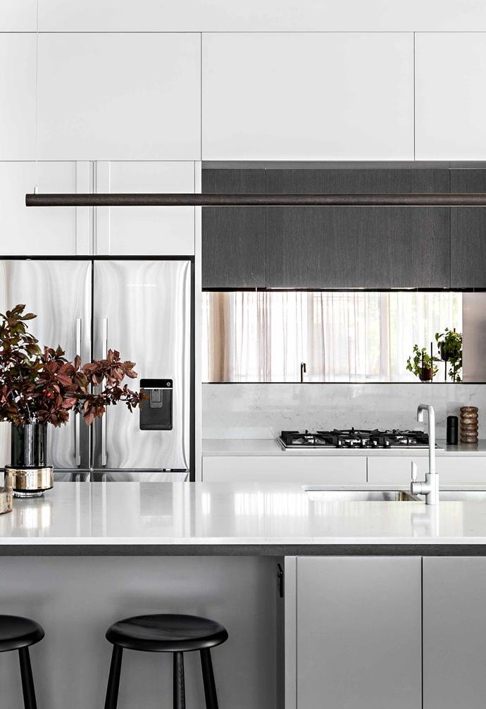 """**Kitchen** Owner Anna was keen on a grey-based colour scheme, which has been warmed up by dark red accessories and shiny items like the new [Fisher & Paykel](https://www.fisherpaykel.com/au/