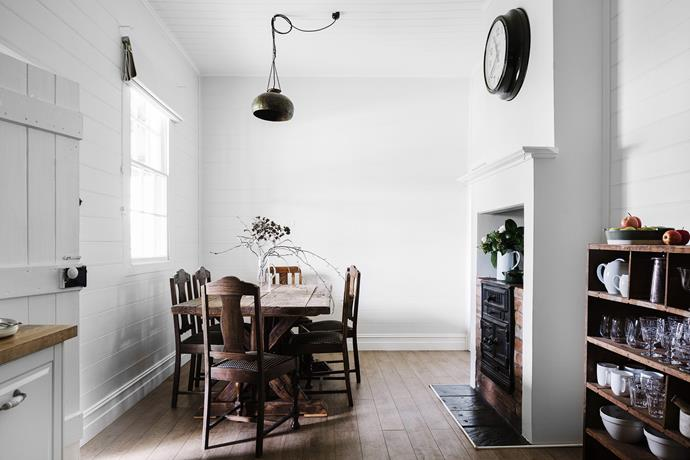 The eat-in kitchen in the cottage has a table from Fossil Vintage surrounded by six antique chairs found on Ebay. The light fitting came from Kyo, while the clock and timber shelves were found in the shearing shed.
