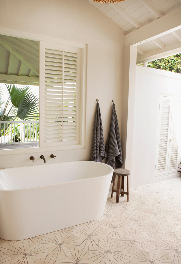 "The resort-style bathroom is completely open to the elements. Everything from the recycled wood mirror to the natural stone basin and wall sconces were designed by Magali. Earthenware sourced from [local antique shops](https://www.homestolove.com.au/vintage-furniture-shopping-8244|target=""_blank"") and a jute floor cushion and rug add to the spa-like experience."
