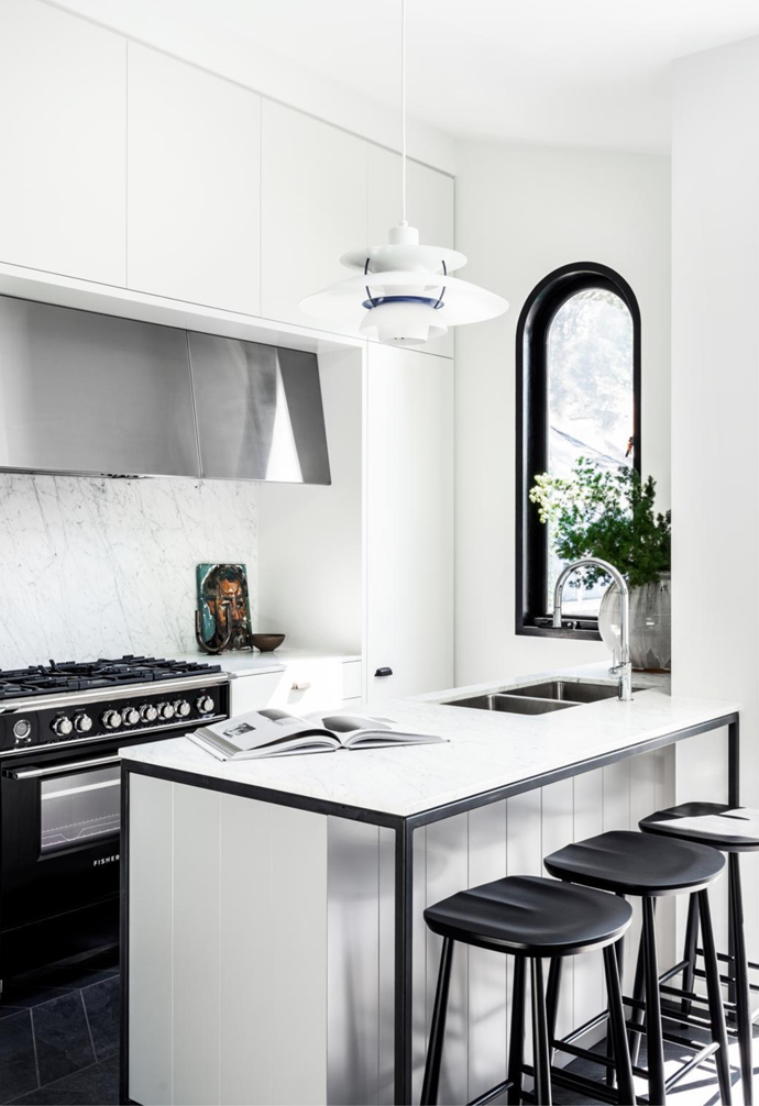 Benchtop and splashback in Carrara marble from CDK Stone. Fisher & Paykel stove, Qasair rangehood and Franke 'Eos' tap, all from Winning Appliances. Ercol Originals bar stools from Temperature Design. Louis Poulsen 'PH5' pendant light by Poul Henningsen from Cult. Artwork from The DEA Store. Candleholder from Space. Glazed vase from Planet. Artesia tiled floor laid in chevron pattern from Skheme.
