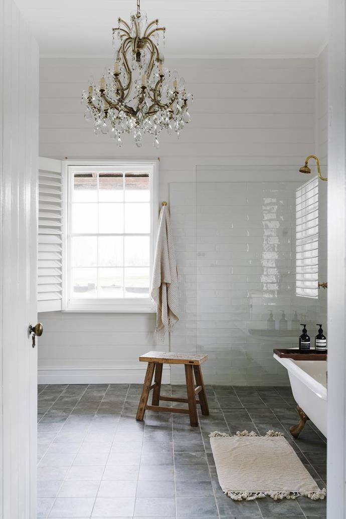 "The antique French chandelier was bought from a dealer in South Australia for this exquisite, and otherwise pared back bathroom in the [Cottage at Dunmore Farm](https://www.homestolove.com.au/dunmore-cottage-farmstay-victoria-20345|target=""_blank"") in Victoria."