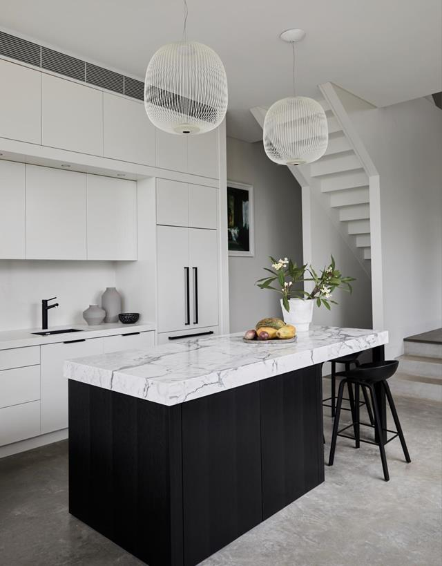 "This [fashionable home's](https://www.homestolove.com.au/fashion-editors-designer-home-21275|target=""_blank"") kitchen is white with black accents and a show-stopping island topped with Calacatta marble.""We didn't want a sink on the island, we preferred to keep it clean and beautiful,"" says owner Kellie Hush."