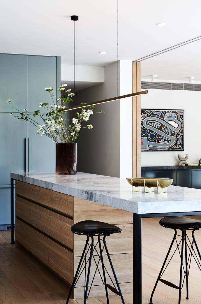 The kitchen serves as the hub between the formal dining and informal living rooms, continuing themes of the joinery and paint colour from the adjoining spaces.