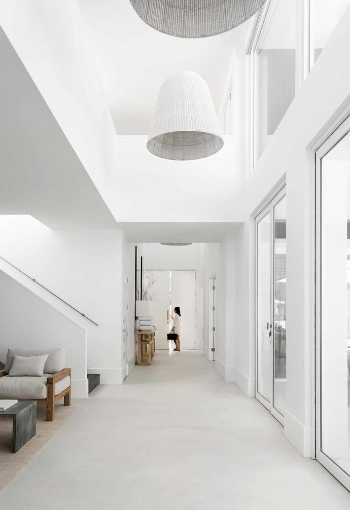 "**Entry** This wide hall stretching from the front door has a light-admitting void overhead and an alfresco area to the right. Interior designer Chris says the key to getting an all-white interior right is layering the space with texture, natural materials and light. The walls are painted [Dulux](https://www.dulux.com.au/|target=""_blank""