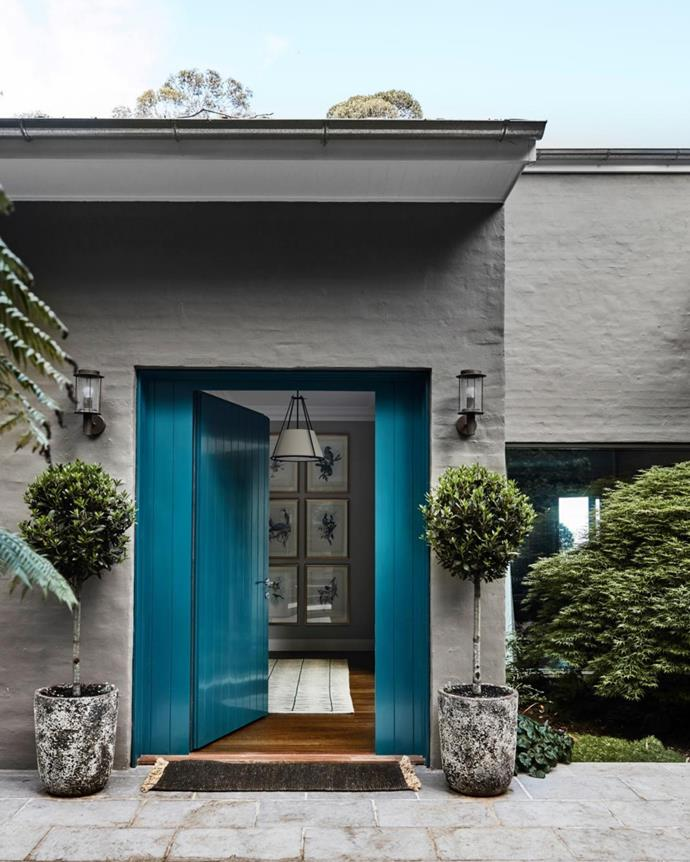 Exterior painted in Dulux Rattlesnake; front door painted Dulux Submarine. Potted bay trees (Laurus nobilis) stand sentinel by the door.