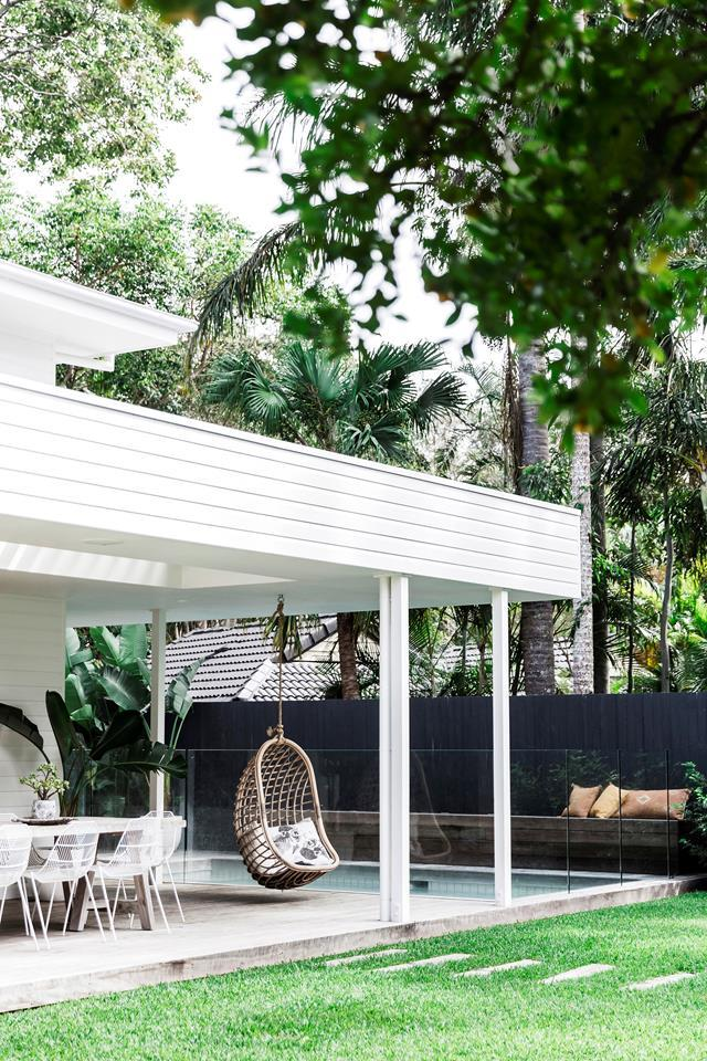 """With sprawling lawns, a hanging chair and a pool, the garden in this [coastal weatherboard home in Byron Bay](https://www.homestolove.com.au/a-coastal-weatherboard-home-byron-bay-19669