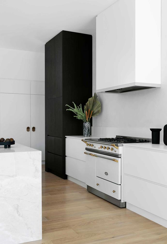 **Kitchen** A black pantry cupboard contrasts dramatically with the mostly-white kitchen space.