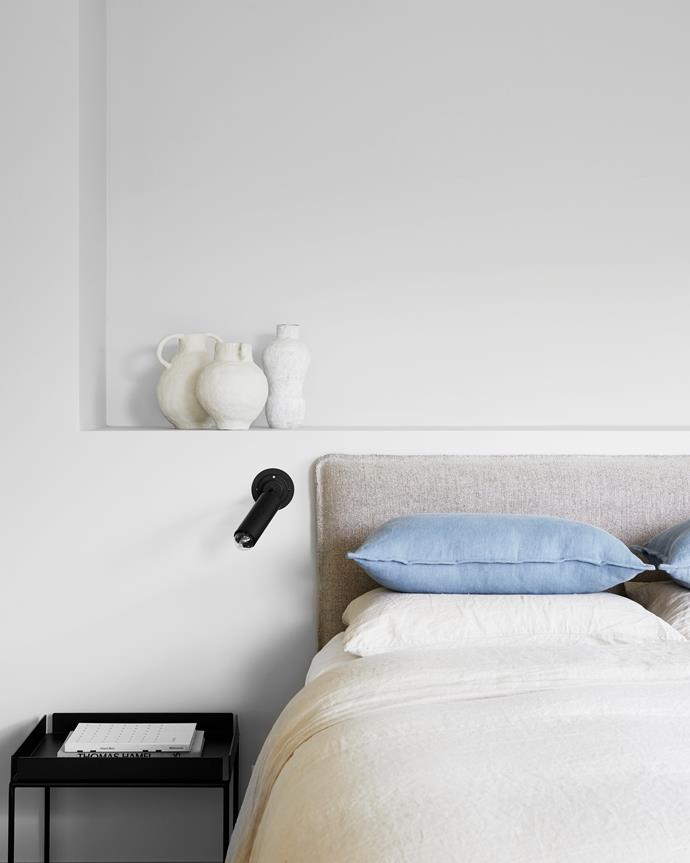 Custom bedhead upholstered in Antwerp Stonewashed linen, Westbury Textiles. Linen quilt cover, Cultiver. Vintage wall light, The Vault Sydney. Side table, MCM House. Ceramic objects by Emma Gale.