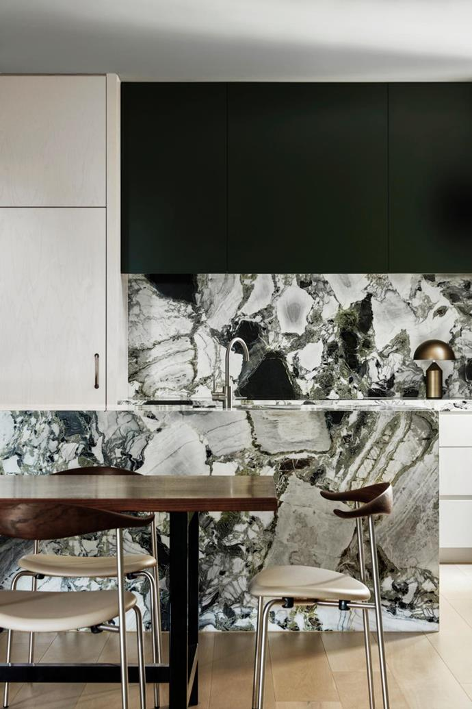 The island bench and splashback are both swathed in vibrant 'Nisava' marble from Signorino. Oluce 'Atollo 239' lamp from Euroluce sits beneath the kitchen cabinetry finished in Dulux 'Vintage Green'.  'CH88P' dining chairs designed by Hans J. Wegner.