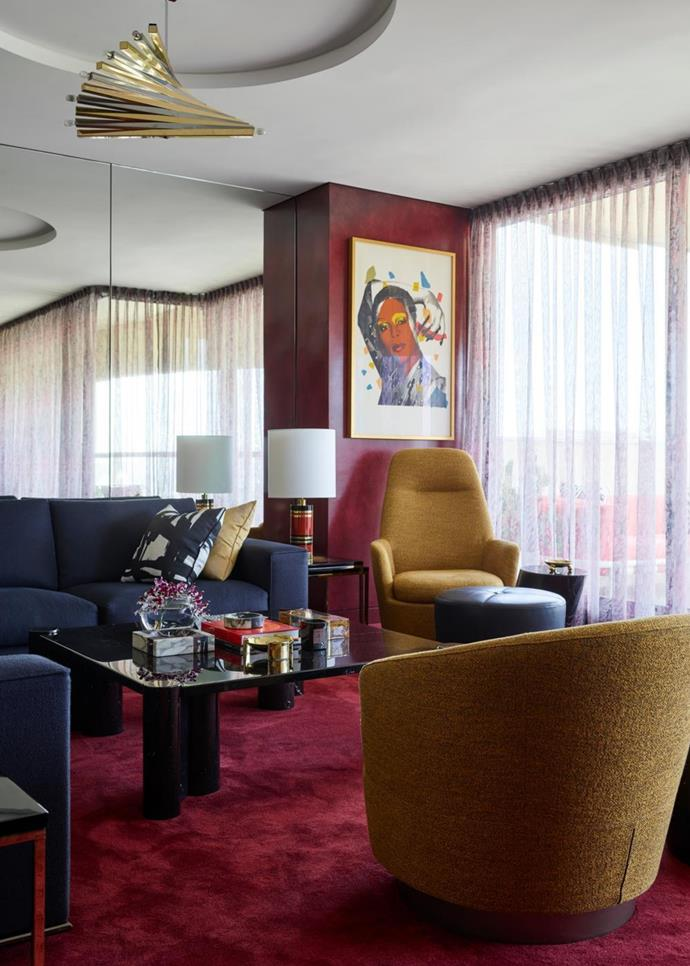A vintage Sciolari pendant hangs above Minotti upholstered armchairs and a work by Andy Warhol.