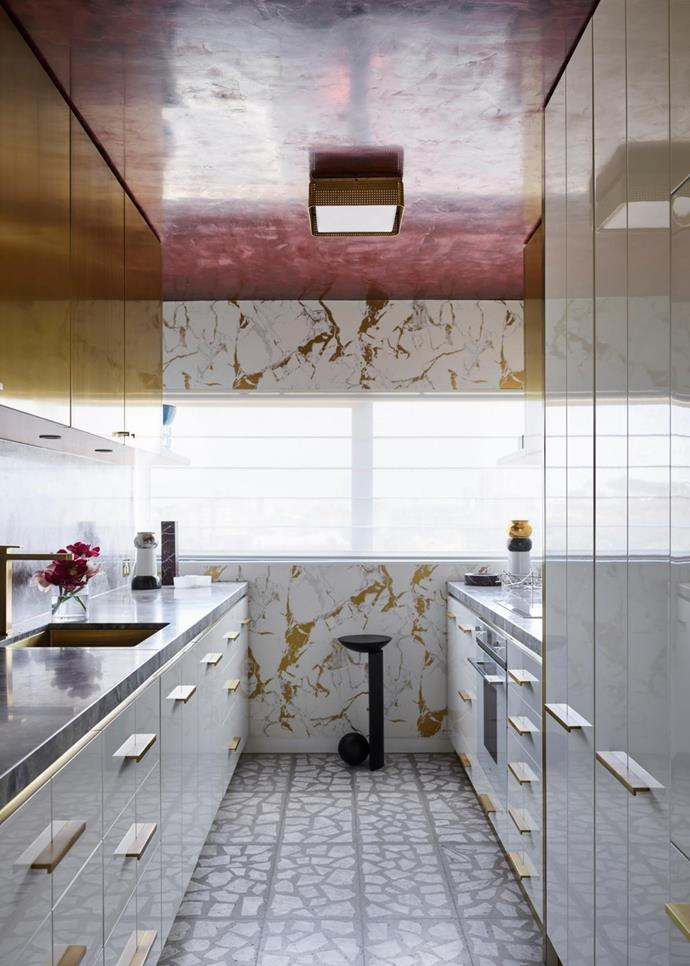 In the kitchen, ceiling lights by Kelly Wearstler, custom joinery with brass-wrapped doors, floors in custom Palladiana terrazzo tiles, and a 'Coito' sculptural table by Pedro Paulø-Venzon.