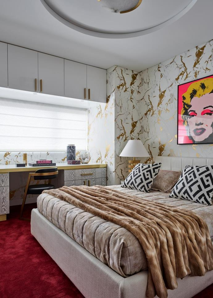 In the master bedroom is a Minotti bed with custom cushions made using Diane von Furstenberg textiles beneath an artwork by Andy Warhol. Office chair by Kelly Wearstler and marble accessories by Greg Natale.