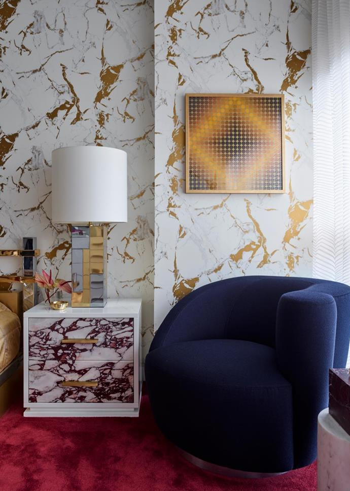 An artwork by Hungarian-French artist Victor Vasarely dazzles against Greg Natale wallpaper for Porter's Paints above a custom timber and marble bedside table, also by Greg Natale. The vintage lamp is by Paul Evans and the vintage armchair is by Vladimir Kagan.