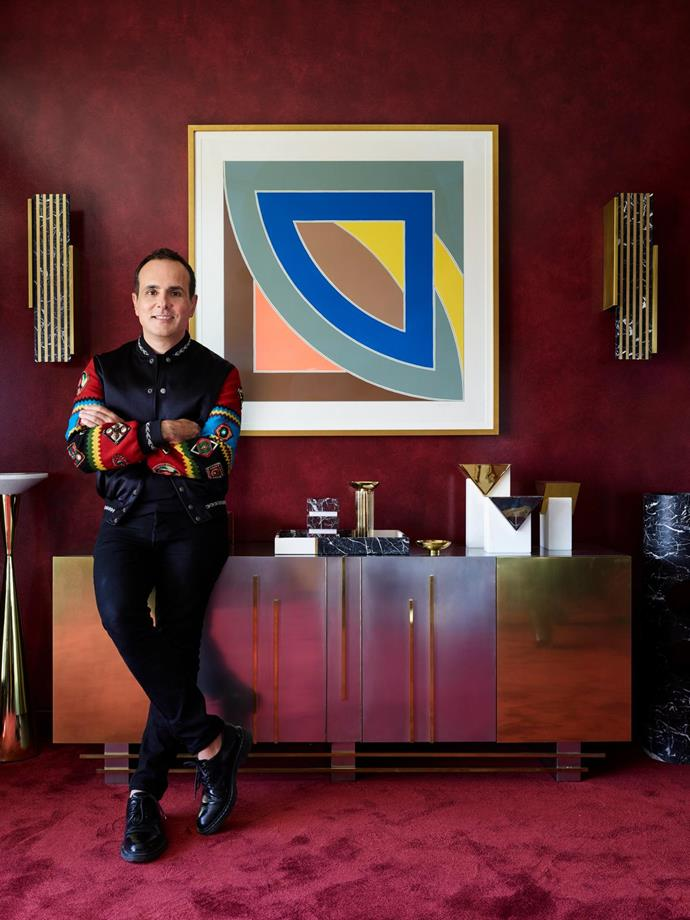 Greg Natale stands beside a vintage French buffet topped with brass and marble accessories from his own collection and the 'Invisible Cities XL' series by Hava Studio. 'Dynasty' marble and brass sconces by Greg Natale flank a Frank Stella artwork.