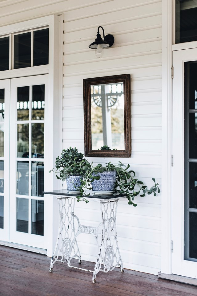 "This wide, [wrap-around verandah](https://www.homestolove.com.au/relocated-farmhouse-renovation-hunter-valley-21749|target=""_blank"") is the place where kids ride their scooters and bikes and where the family often throws dinner parties and sundowners. This part of the verandah has been styled with a vintage singer sewing table and a pair of succulents in pots."
