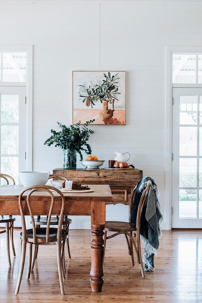 The antique table is surrounded by Bentwood chairs. The Margo by Vynka Hallamm hangs above an old butcher's block. Diptyque candle from Mecca.