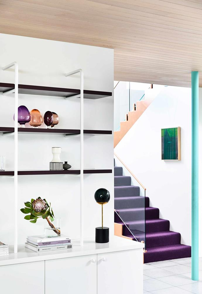 The vibrant purple staircase and warm timber ceiling panelling add warmth to the all-white palette in this home by Doherty Design Studio.