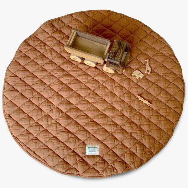 """Quilted Linen Baby Play Mat in Rust, $154.95, [Warren Hill](https://mywarrenhill.com/collections/french-linen-baby-playmats/products/quilted-linen-baby-play-mat-rust