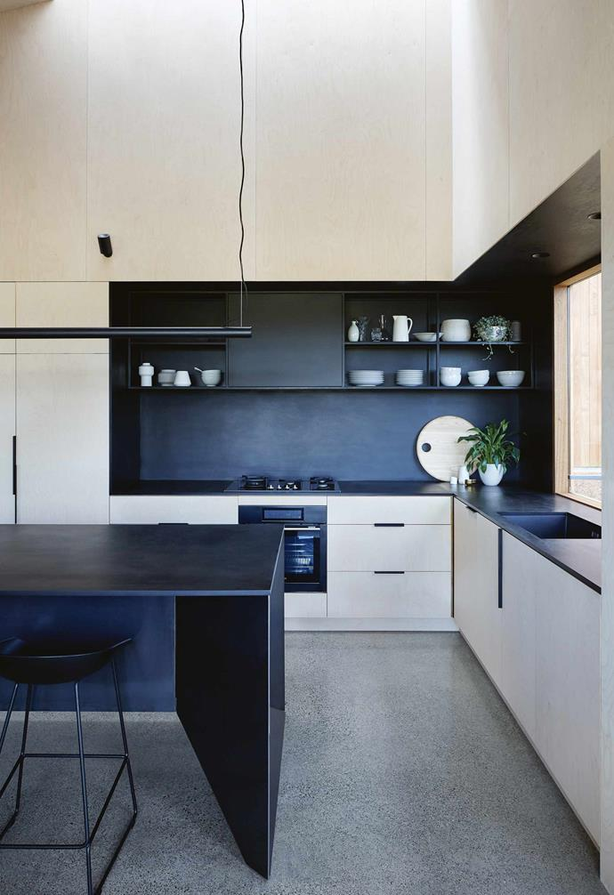 """The kitchen, dining and living zones have been cut into the ply-clad shell of the home, along with built-in seating and storage. """"We carved the conversation areas into the thickness of the walls,"""" says Mick. In the kitchen, different layers are exposed and cut out from the ply shell, with black Paperock surfaces revealing the depth of the building.<br><br>**Kitchen** Preparation areas are cut into the plywood 'skin', with the niche lined with Paperock, a composite of resin and recycled paper. The worktops are lit from within the niches, with up-lights bouncing soft lighting off the raked ceiling. A 'Phoebe' LED pendant light from [Masson For Light](https://www.massonforlight.com.au/