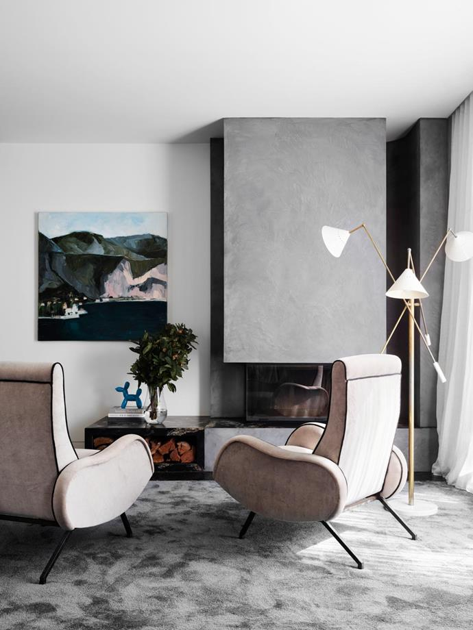 In the restful master bedroom, the mid-century recliners and Italian floor lamp are vintage, the painting is by Sally Joubert and the rug by Halcyon Lake. The fireplace is rendered in Waterstone polished plaster from Bishop Master Finishes.