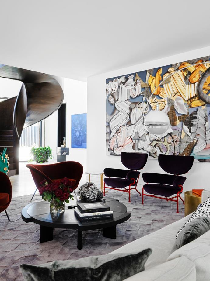 Artwork by Gregory Hodge. A Maxalto 'Omnia' sofa and Cassina 'Tre Pezzi' armchairs with red metal frames and upholstery in Kvadrat 'Harald', all from Space. Molteni&C 'D.154.2' armchairs from Hub. The Cassina '529 Rio' coffee table from Space, on which sits Peter Cooley's Echidna 2 sculpture, is accompanied by a Baxter 'Loren' circular brass side table from Criteria and Marta Sala Éditions 'T1 Harry' marble and metal side table. Rug from Halcyon Lake. By the staircase is a Dane Lovett painting from STATION gallery.