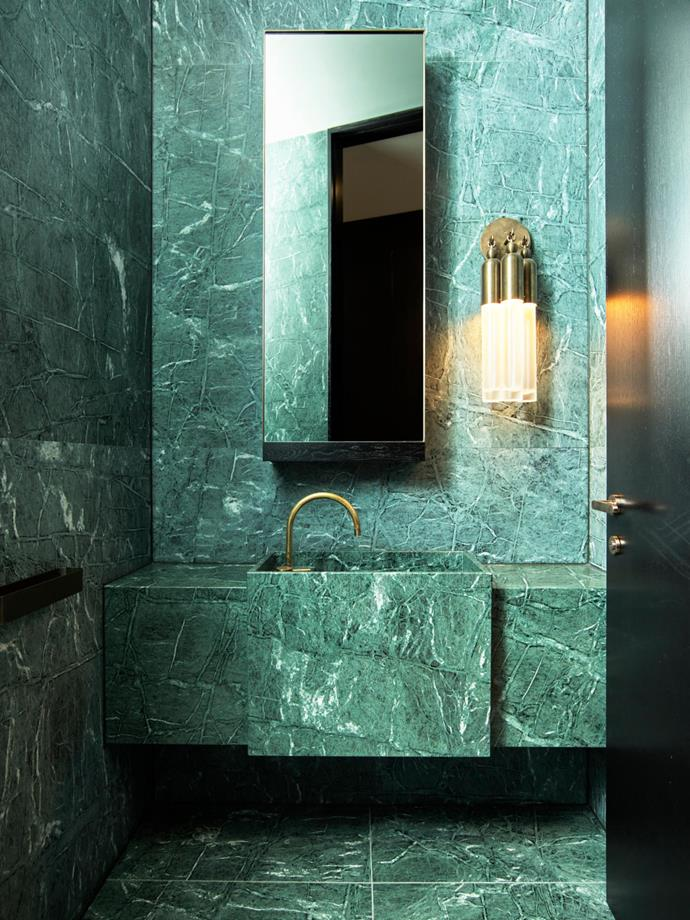 The powder room is realised in Ocean Green marble from Parthenon Marble. Flack Studio designed the custom basin, its chiseled form adding dimension to the immersive scheme. Aged-brass accessories include the Astra Walker 'Icon' mixer, Apparatus 'Tassel 3' sconce from Criteria and custom towel rail.