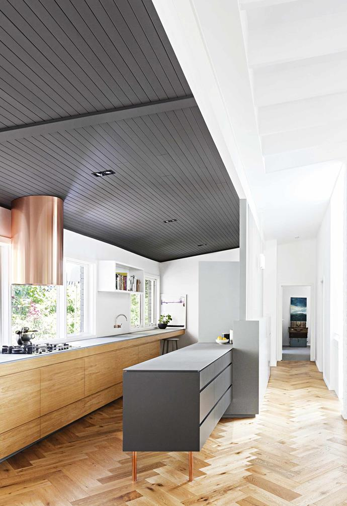 """**Kitchen** Owner Lynelle describes her old kitchen as """"dark, hot, and awkwardly boxed in"""". Architect Alison Nobbs created a design that made the most of the views and connected the cooking zone to the living space. Painting the ceiling in a dark grey highlights the change in height and helps zone off the area."""