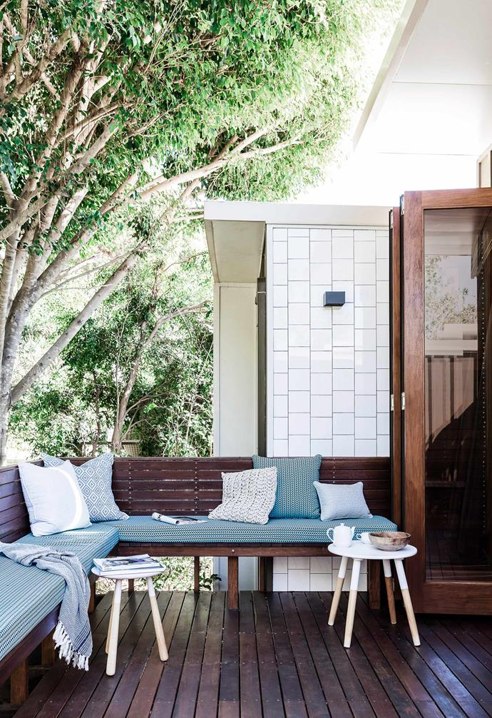 The stained spotted-gum deck of this North Stradbroke Island home provides a rich contrast to its leafy backdrop.