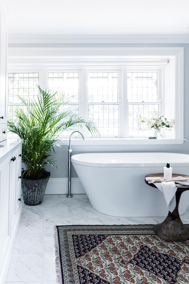 "A verdant and leafy fern sits next to the bathtub in this [free-flowing Sydney home](https://www.homestolove.com.au/hamptons-style-makeover-of-a-1940s-sydney-home-6897|target=""_blank""), adding a natural touch."