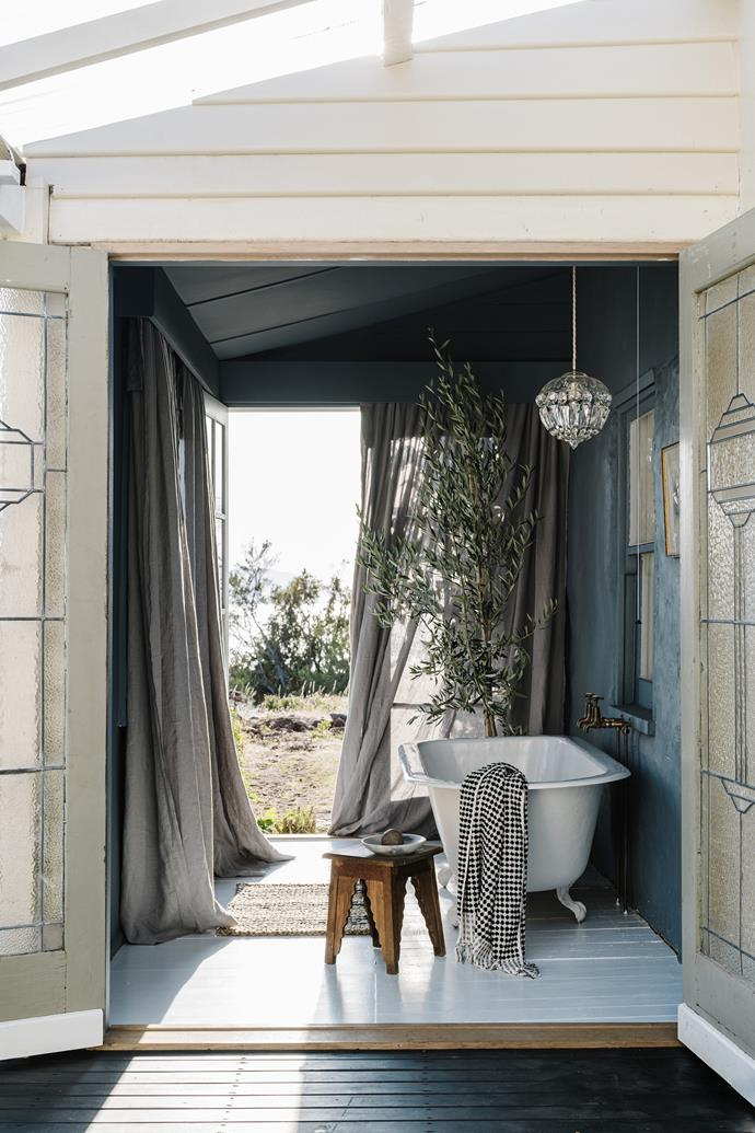 "An olive tree transforms the outdoor bath space in this [Tasmanian abode](https://www.homestolove.com.au/the-burrows-swansea-tasmania-21597|target=""_blank""), adding a relaxed Mediterranean feel."