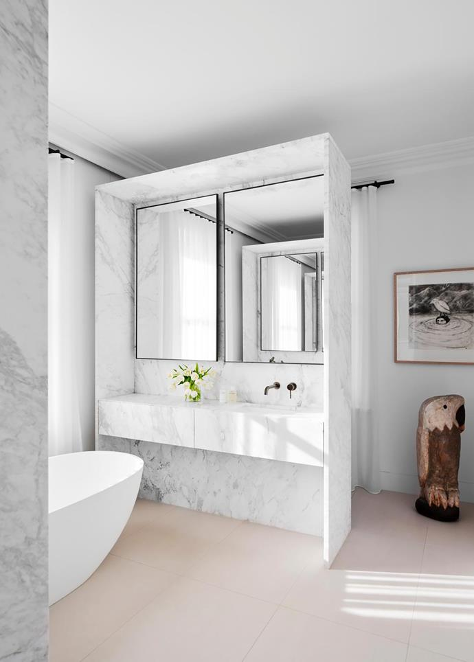 In the master ensuite, marble boxes separate bath, shower and toilet. Laverna marble from Euro Natural Stone. Brodware 'City Stik' tapware in Aged Iron. Moda 'Teresa' freestanding bath from ACS Bathrooms. Bird sculpture and artwork by Bruce Armstrong.