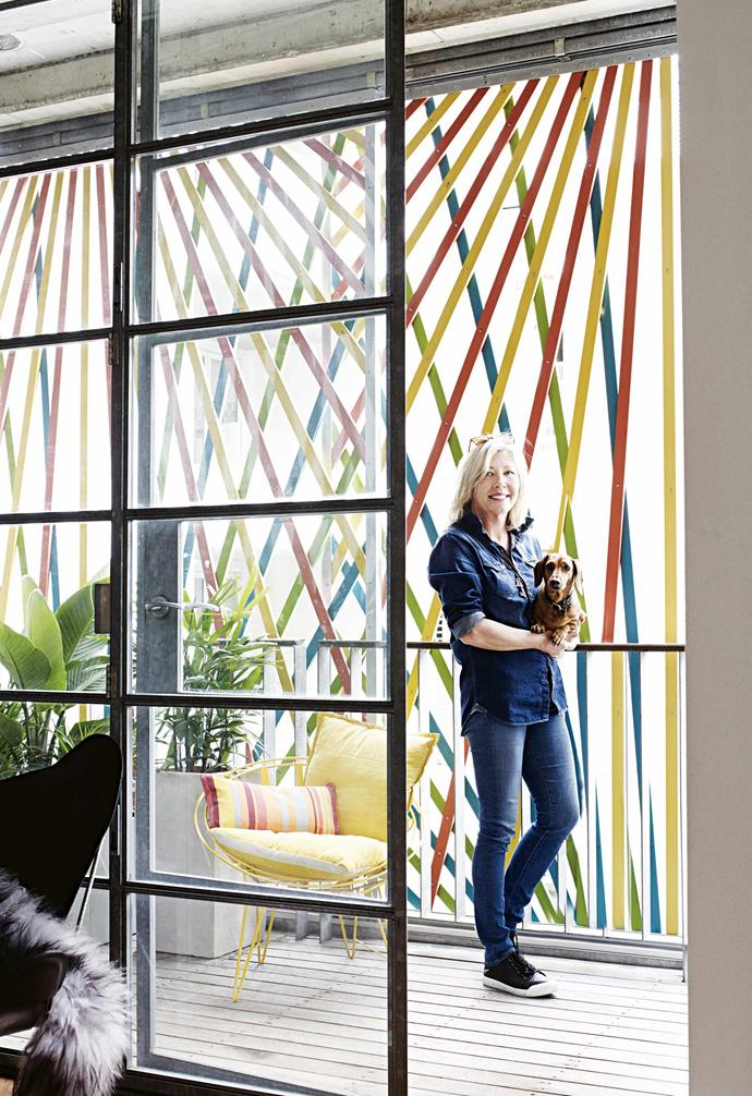 "**Balcony and living area** The coloured screen influenced decor decisions, says Stephanie, whose instinctive style is more monochrome. ""You have to embrace colour in this space otherwise it would look drab."" The niche allows her to display a vignette of ceramics from Parterre and Walker & Beck. According to Stephanie, artist Matthew Johnson, whose parents used to exhibit in the gallery, remembers spending hours in the building playing with pick-up sticks as a child – that game informed his design for the privacy screen."