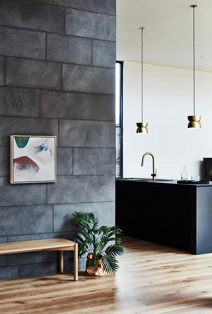 """Small brass pendant lights, paired with brass tapware, are contrasted to the mostly black colour palette in the kitchen of this [Barwon Heads home](https://www.homestolove.com.au/architecturally-designed-ready-to-build-home-5985