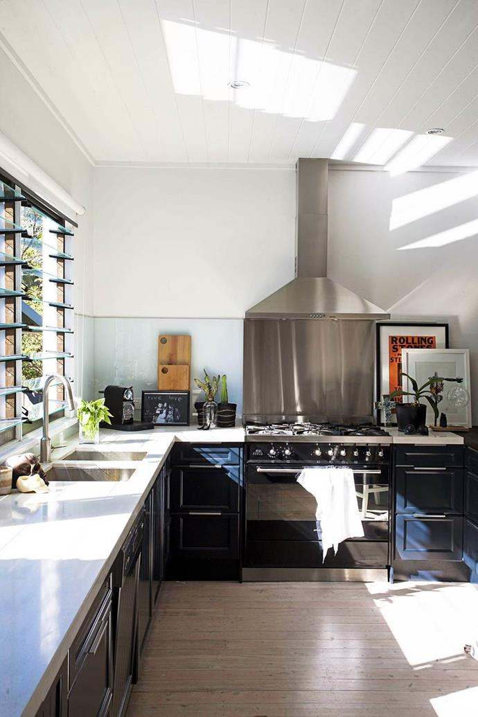 """Sunlight streams through glass louvres into the kitchen all day long. Black cupboards and white benchtops tie in with the rest of the palette in this [charismatic beachside home](https://www.homestolove.com.au/gallery-jamies-beach-house-renovation-1408