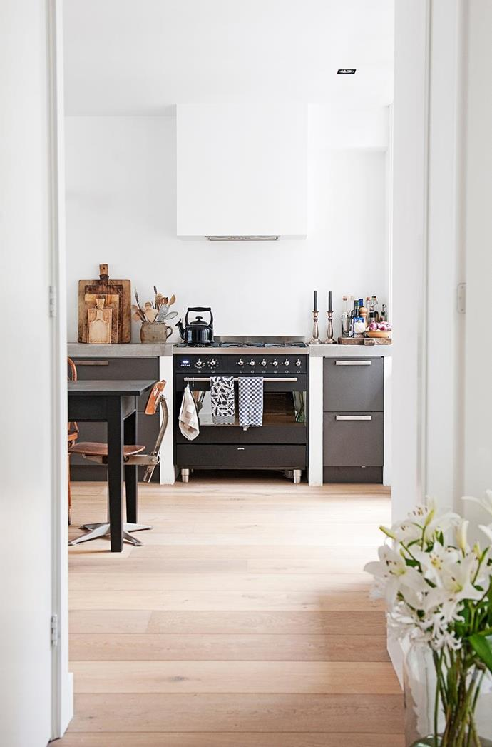"""This pared back kitchen is designed for simple living, with an open-plan kitchen and dining area and a concrete countertop that suits the [simple Scandi-style abode](https://www.homestolove.com.au/a-simple-scandi-style-home-4413