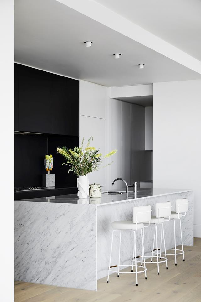 """Handle-free jet-black cabinetry looks sleek, and contrasts with the white marble island in this [contemporary residential development](https://www.homestolove.com.au/george-powlett-apartments-melbourne-20758