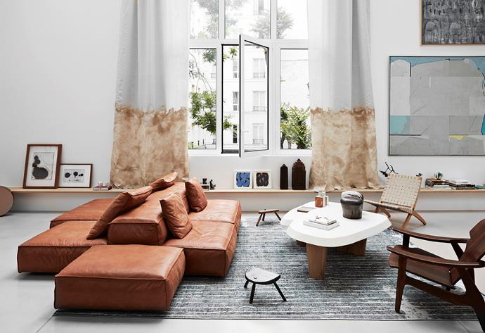 The Living Divani sofa in cognac leather is a sculptural yet comfy centrepiece to the living area, zoned by an antique rug Amélie sourced from Iran. Pierre Augustin Rose coffee table are ceramic bottles by Guido Gambone and wooden sculptures by Milo Momcilo. The woven Hans Wegner easy chair and large timber Sergio Rodriques chair get that effortless mismatched look just right.