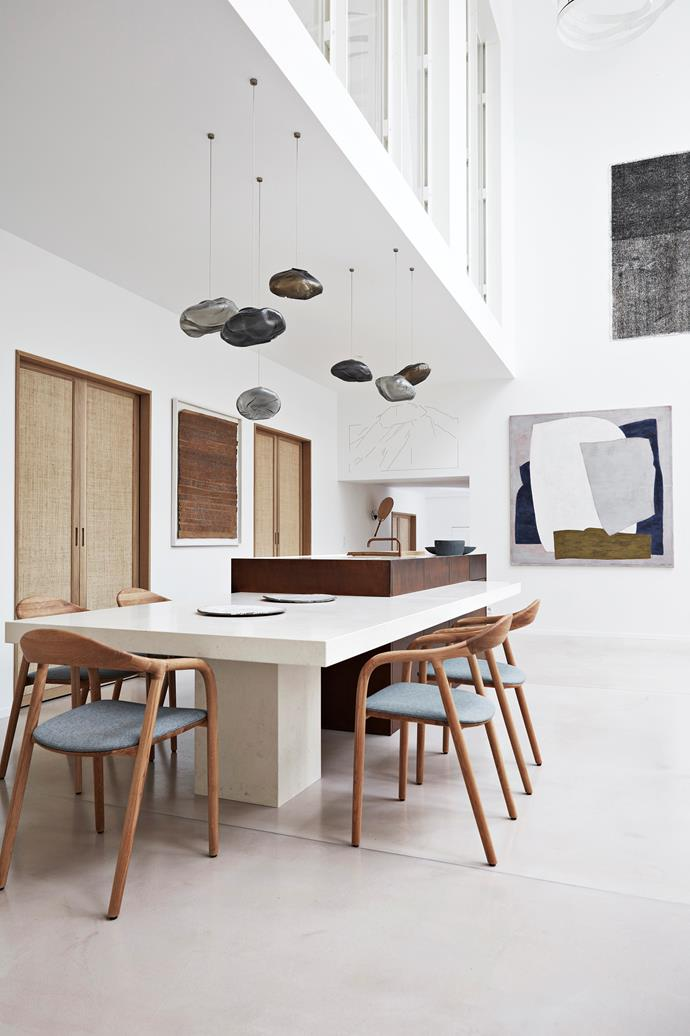 The kitchen island is clad in browned iron with an attached Paloma stone dining table – a space-saving design feature that has been cleverly zoned by some overhanging Bocci Murano glass lamps.