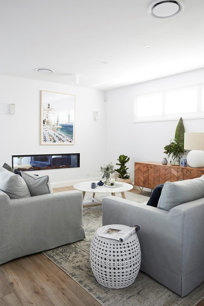 "An atmosphere of informal luxury permeates the main living area, thanks in part to a double-sided Real Flame fireplace that gives a glimpse of the formal lounge beyond. ""Robyn wanted this room to feel very relaxed, so we used soft colours rather than layering lots of pattern,"" says Natalee of a space that features two dive-into Melbourne-made sofas from [Molmic](http://www.molmic.com.au/