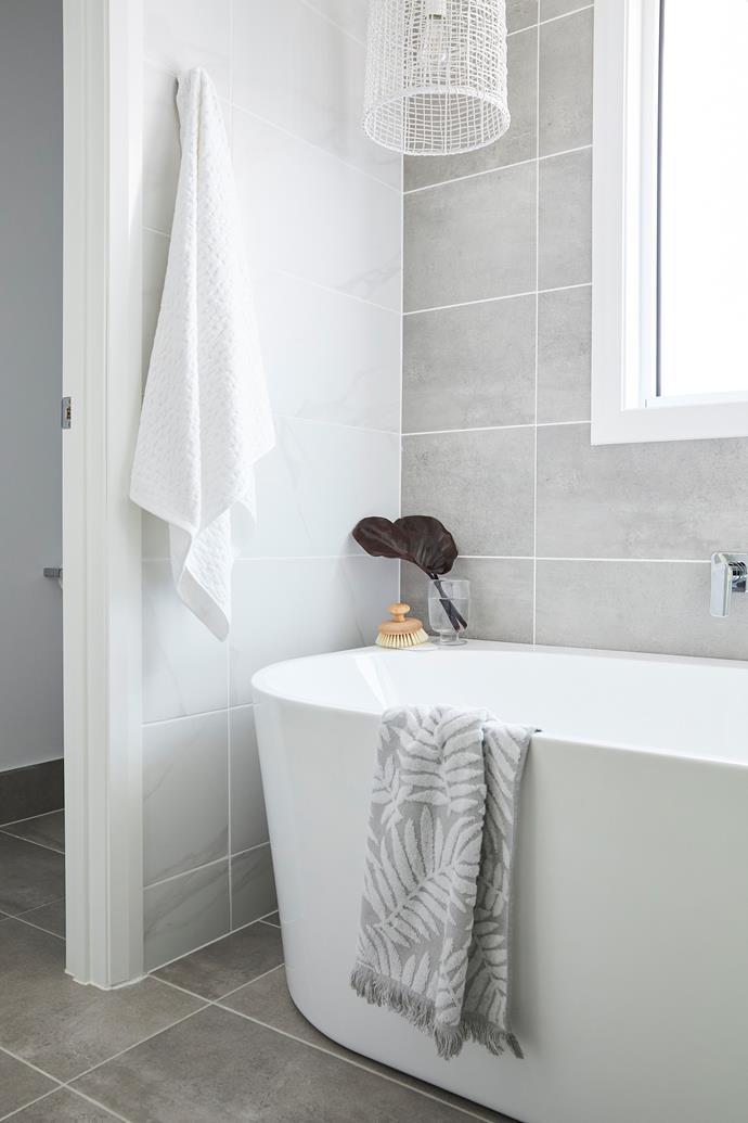 "Robyn and Jonathon's serene five-star ensuite includes an indulgent Caroma 'Aura 180' freestanding bath. Robyn added extra skylights during the design phase to ensure the space was flooded with natural light, an effect enhanced by 'Belga Grey' porcelain tiles from Beaumont Tiles. A woven white 'Coral' pendant from [Beacon Lighting](https://www.beaconlighting.com.au/|target=""_blank""
