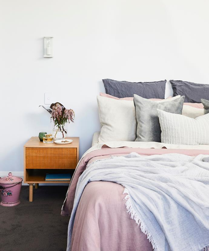 "Layers of beautiful Cultiver bedlinen and misty velvet cushions from Tara Dennis Store give an air of easy going elegance. ""I've got touches of pink that Jonathon doesn't like, but I thought, 'If there's any way I can get away with pink, it's a dusty pink like this one,'"" says Robyn. ""That way it doesn't look too girly."" The muted tones marry beautifully with deep charcoal 'Alberta' carpet from Accent Carpets."