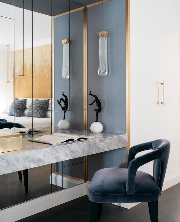 In the guest suite, a statuette belonging to the owners sits on a desk custom-made in Laverna marble with a chair upholstered in velvet. The custom mirror wall trimmed with brass reflects the Articolo 'Fizi' wall sconce from Est Lighting.