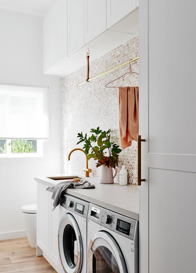 "Penny round tiles make a beautiful feature in this [glamorous laundry](https://www.homestolove.com.au/glamorous-laundries-19386|target=""_blank"") and provide a warm, modern rustic feel. The pink and trendy terracotta tones are complemented by touches of brass and leather while oak timber flooring keeps the look light and natural and is easy to clean."