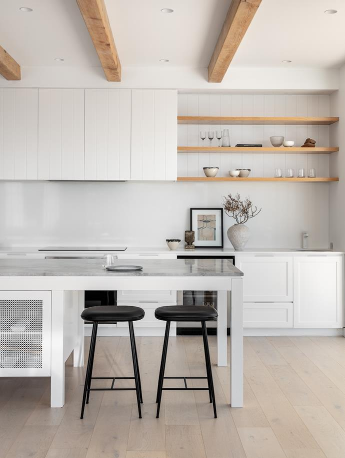 The kitchen island stone is Super White Dolomite, while the benches and splashback are Smartstone. Black metal stools from Great Dane. Ceramics by Brett Stone from Utopia Art and Alana Wilson Studio, artwork by James King from Becker and Minty.